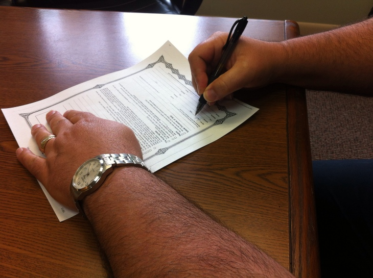 Man signing a contract.