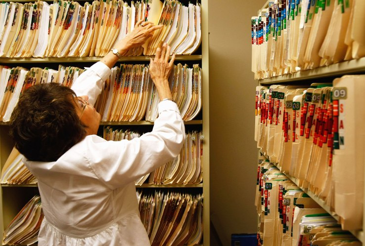 WALSENBURG, CO - AUGUST 05: Clinic office assistant Joan Vest searches for a patient's missing medical file at the Spanish Peaks Family Clinic on August 5, 2009 in Walsenburg, Colorado. The Spanish Peaks Regional Health Center, which treats rural residents from throughout southern Colorado, plans to move to an electronic health records system before the end of 2010. Administrators say they expect the costs of upgrading the system will eventually be recovered through federal funds, as part of the overhaul of the nation's healthcare system. (Photo by John Moore/Getty Images)