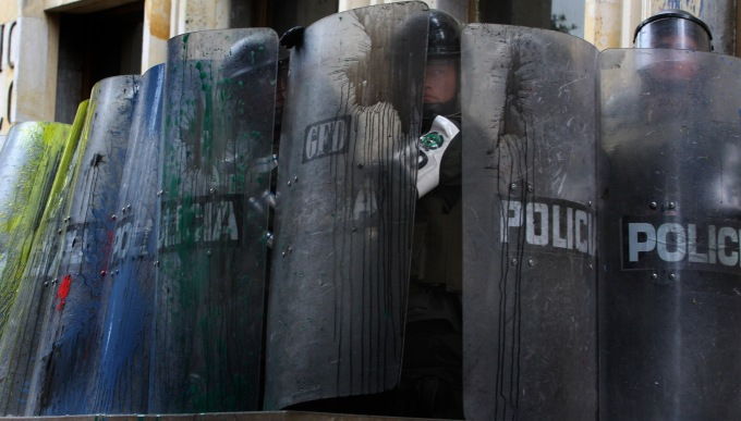 A group of police cover their bodies as an observes during a May Day march through the streets of Bogota, Thursday, May,1, 2008. (AP Photo/William Fernando Martinez)