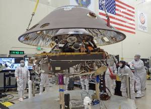 The back shell of the InSight spacecraft is lowered onto the lander in a clean room at Lockheed Martin.