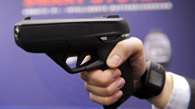 "An employee of Armatix poses for photographers as he presents the ""SmartGun Concept"" at the International Weapons trade fair in the southern German city of Nuermberg on March 12, 2010. 1150 exhibitors are taking part in the trade fair running to March 15, 2010. (Photo: JOERG KOCH/AFP/Getty Images)"