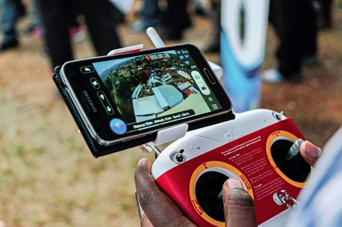 A photo taken on July 24, 2014 shows an aerial view displayed on a mobile phone synchronised to a tele-guided drone camera during an international trade fair in Kigali. Rwanda is planning to construct a droneport in order to get drones to carry mostly medical urgent supplies from a central hub to rural areas around the country. (Photo: CYRIL NDEGEYA/AFP/Getty Images)