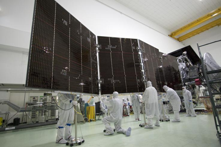 Workers at Astrotech stow one of the enormous solar panels that power Juno.