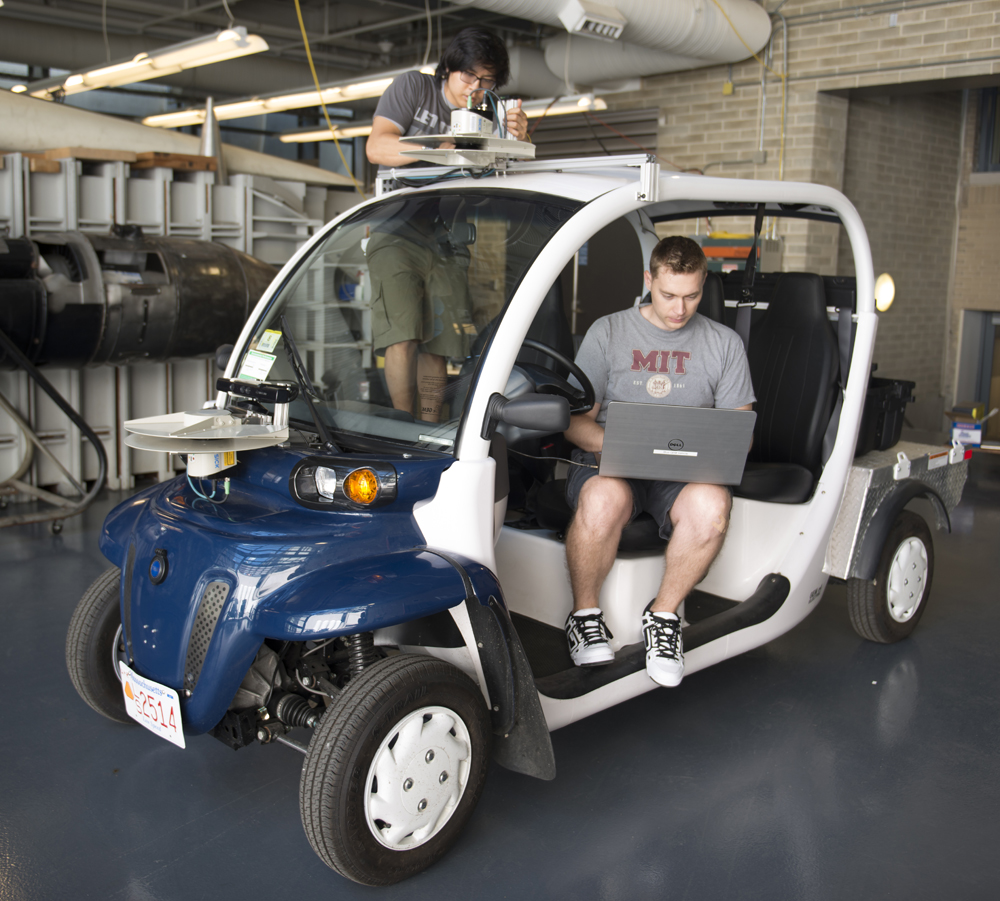 Graduate student Justin Miller and undergrad Wally Wibowo of the Aerospace Controls Lab working on vehicles outfitted with sensors that match those of self-driving cars. This work is part of the Ford-MIT Alliance and aims to predict pedestrian behaviors on short time-scales while also providing data to support a mobility-on-demand system for the MIT campus.