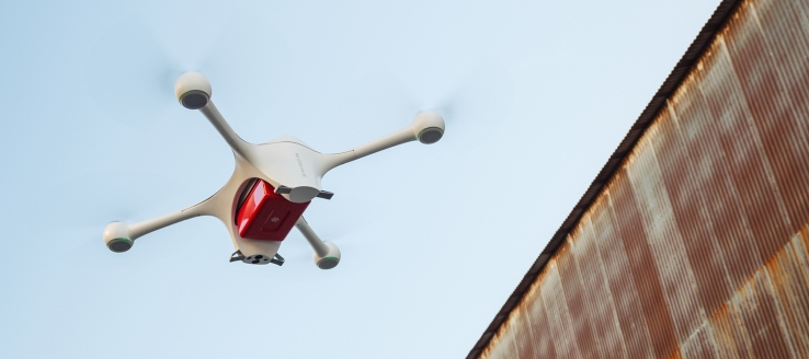 A self-flying, Matternet 2 drone hoists a package near a shipping container.