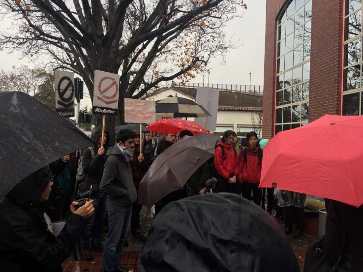Dozens of protestors huddle in the rain outside Palantir.