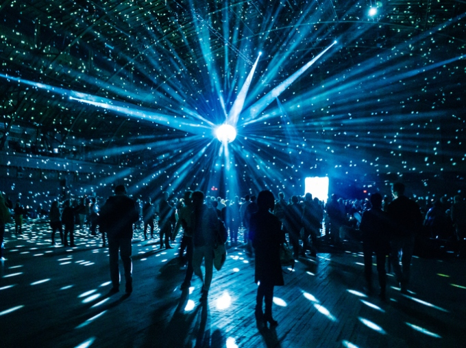 Illuminated Disco Ball Over Silhouette People In Nightclub