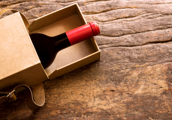 A bottle of wine escaping from a gift box. Still life.