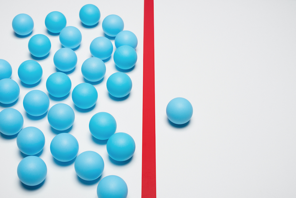 One blue ball on one right side of red line, many blue balls on left side