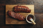 Grilled pork ribs with barbecue sauce on wooden background