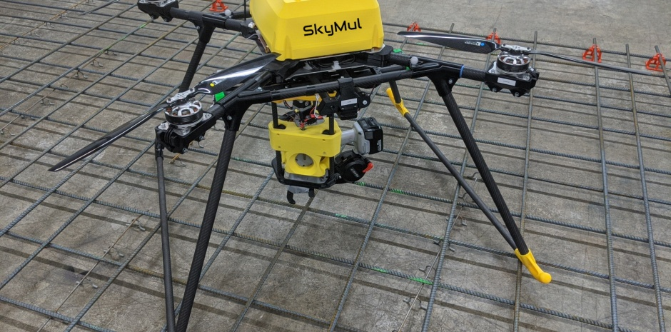 A yellow SkyMul drone with a rebar tying tool sitting on top of some rebar